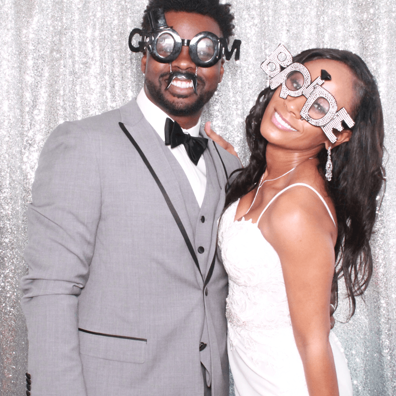 bride and groom in photo booth with glasses and silver glitz backdrop