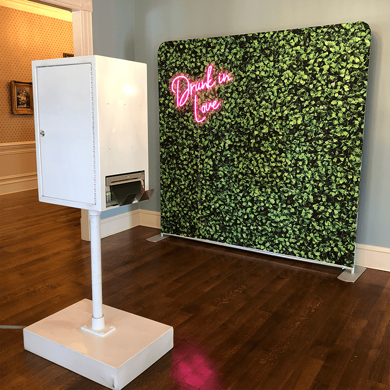photo booth set up with cloth boxwood hedge backdrop